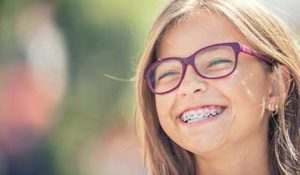dental braces tx, girl with glasses grinning with braces
