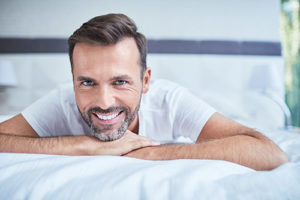 teeth whitening services pearland texas, man on bed smiling